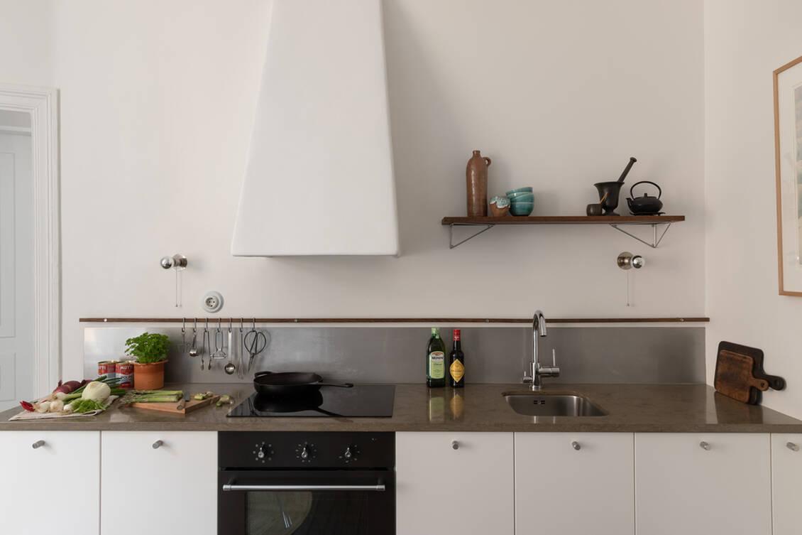 Fläkten och diskmaskinen är integrerade i kökets vita inredning.