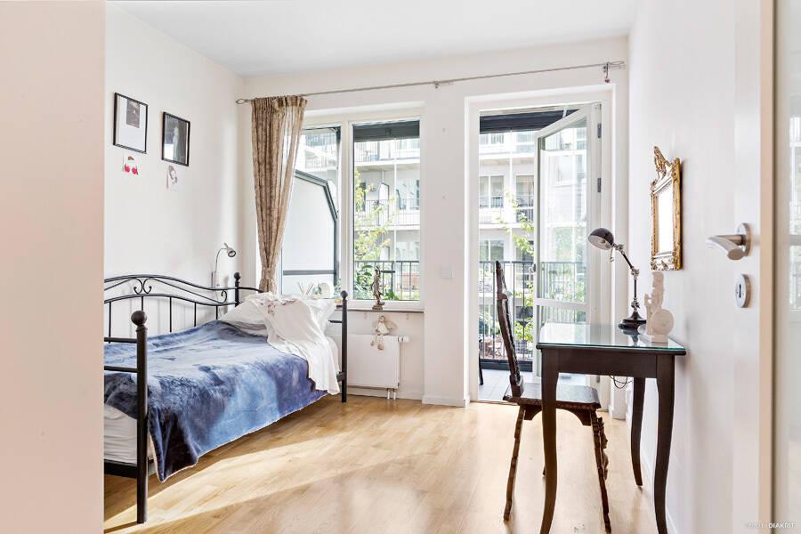 Sovrum med utgång till inglasad balkong.