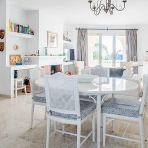 Vardagsrummet med matplats, ljusa väggar och golv