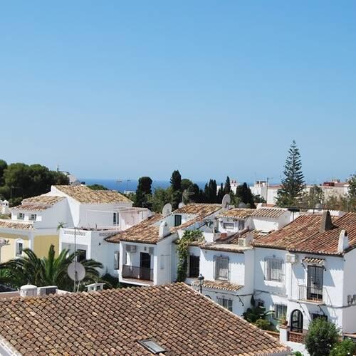 Utsikten från takterrassen över hustaken och havet