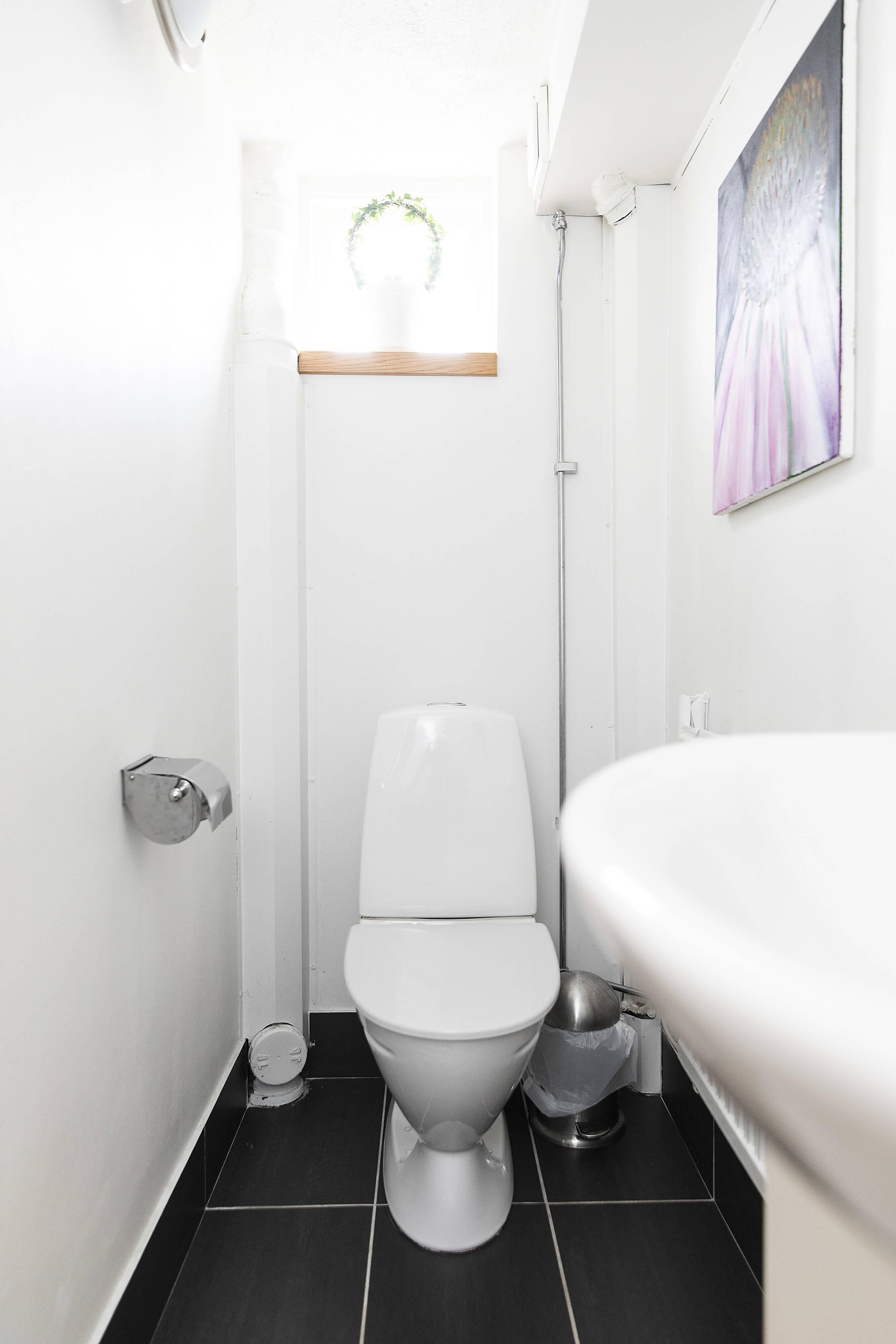 toalett med ljusa väggar o grått klinkergolv